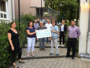 Vertreter von Pro Bockwurst überreichen den Spendencheck an die Vertreterin der Elterninitiative